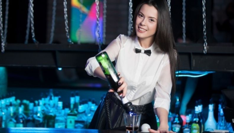 smiling waitress preparing glass