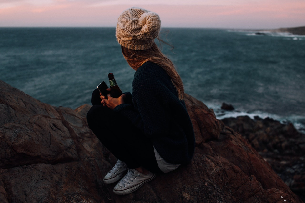 Young girl on a cliff consuming alcohol
